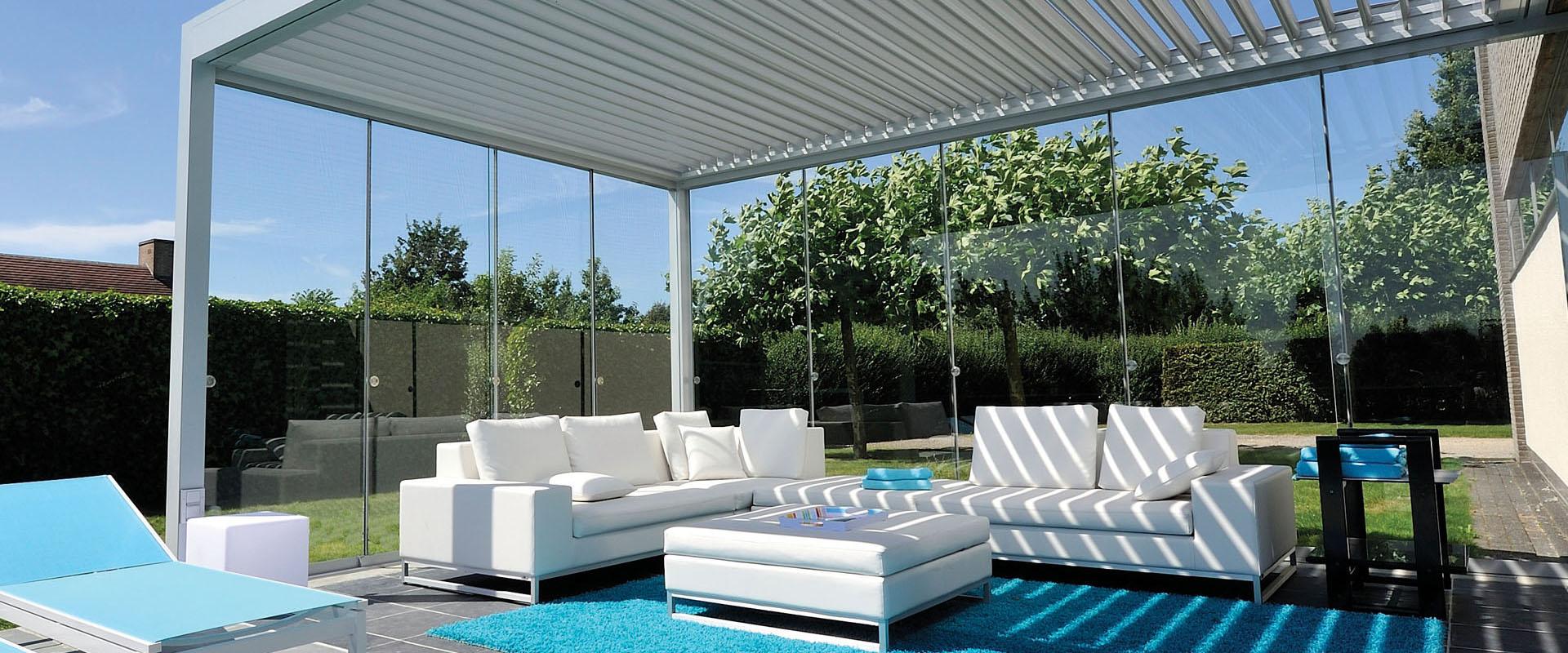 Een foto van een Brustor Tuinkamer met bewegende glasdelen en lamellendak op een terras voorzien van tuinmeubilair.